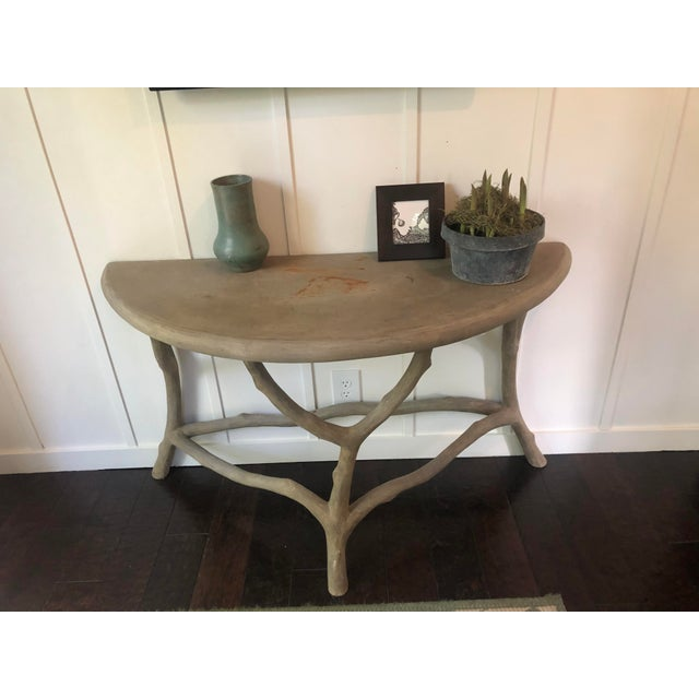 Artisan crafted cast-stone concrete console table or garden table having a demilune form and faux-bois twig branch legs....