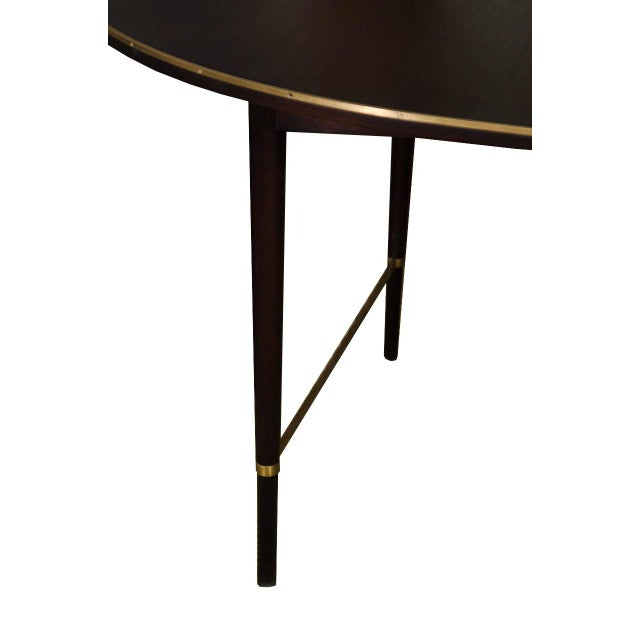 Paul McCobb Calvin group oval dining table.Ebonized mahogany with rich undertones of darkest brown, featuring brass trim...