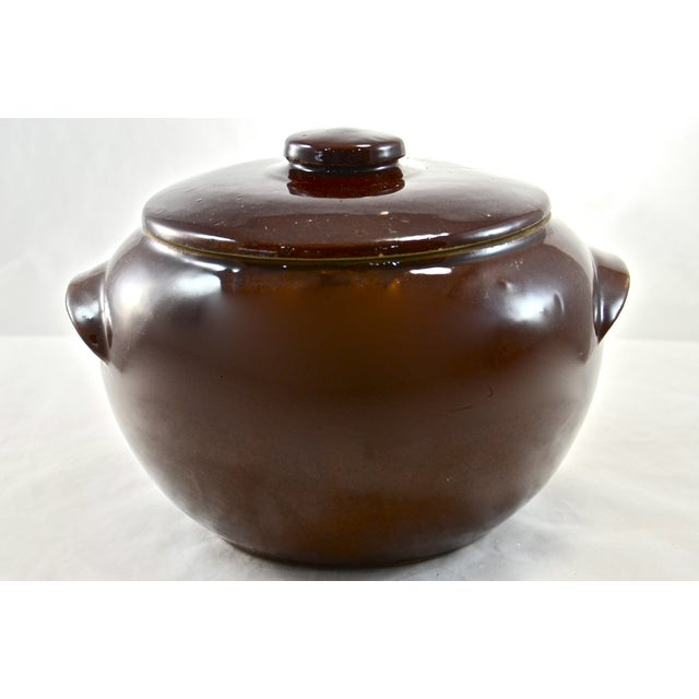"Vintage lidded farmhouse ""bean"" crock or casserole. Decorative warm brown glaze over all. Marked ""USA."""