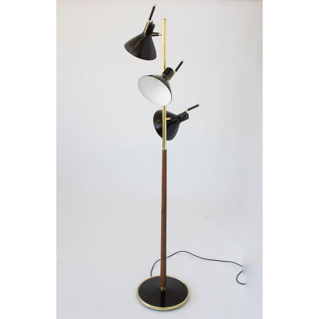 A single column floor lamp in enameled steel, walnut and brass by Gerald Thurston for Lightolier. The lamp has a round...