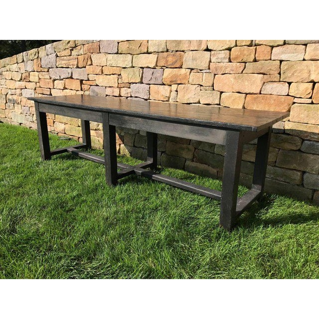 A black painted 19th century farm or work table with a distressed black painted finish. large-scale. Would work well as a...