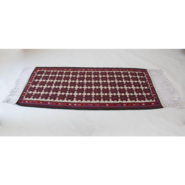 A flat-woven Turkish Kilim from the 1960s, this rug is a runner-style with richly saturated hues and all-over field of...