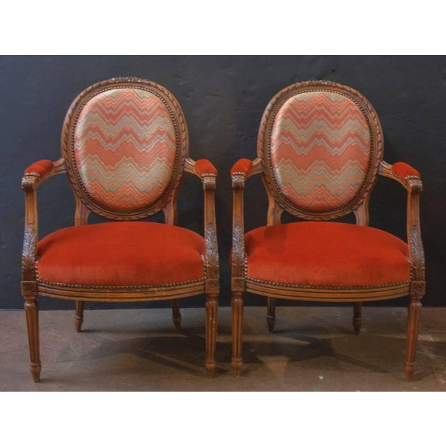 Dating to circa 1900, and carved in the Louis XVI style, this pair of charming armchairs feature the traditional medallion...