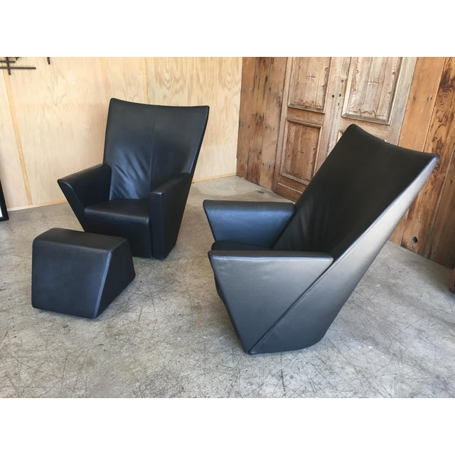 Pair of swivel chairs and ottoman in textured black Italian leather.