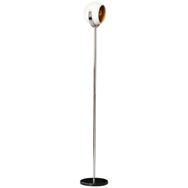 Minimalist eyeball floor lamp in white and chrome with black base in the style of Robert Sonneman. The lamp head is...