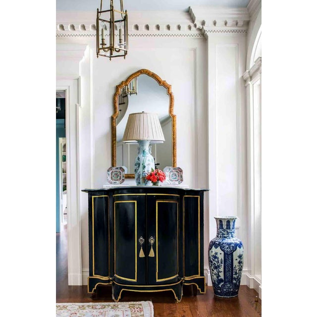 A superb chinoiserie gold and black lacquer commode, the demi-line shaped body is decorated with gold accent. Two doors...