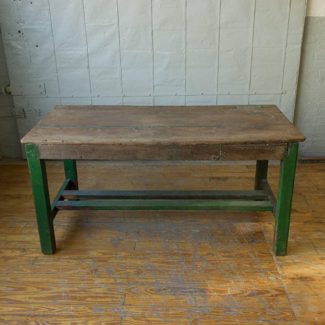French Industrial wooden work table with old green paint patina on the legs and a natural wooden top, early 20th century.