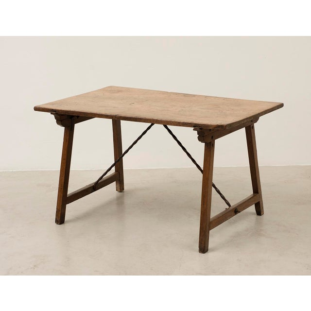 An elegant Spanish walnut travel table with lovely patina. Single plank top with iron stretchers. Spain, 18th century.