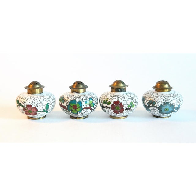 A Wonderful set of cloisonné salt cellars and pepper shakers. Beautiful floral design on brass bowls and shakers. The...