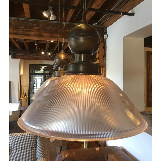 Tasteful holophane glass pendant with brass hardware from Italy.