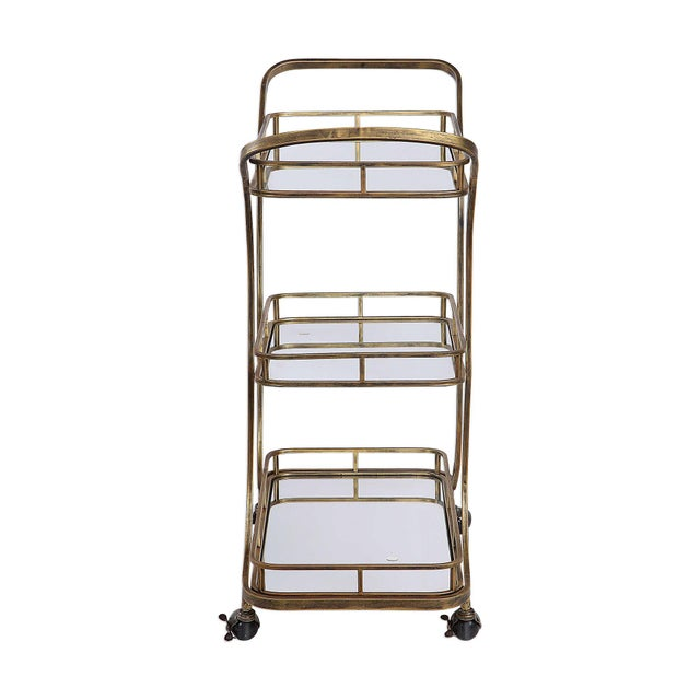 Solid iron transports this transitional bar cart featuring three tray style mirrored shelves finished in antiqued...