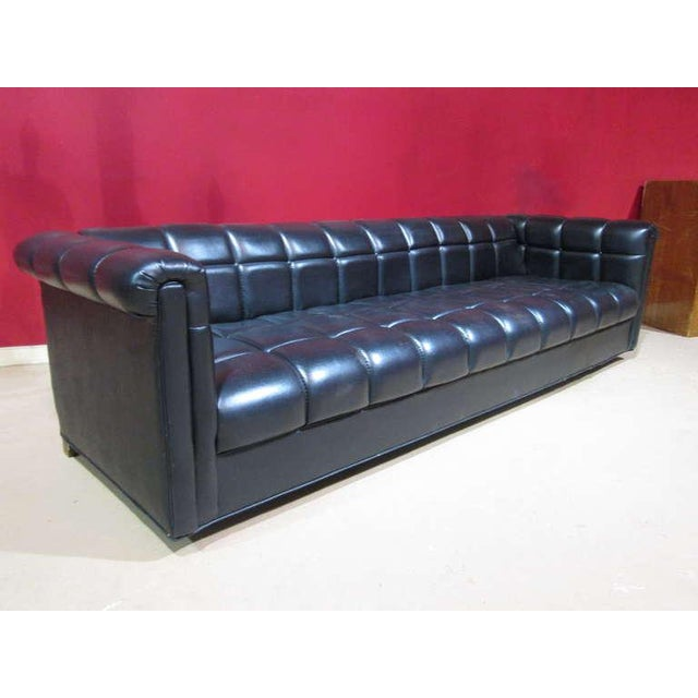 Black, vinyl, tufted sofa with wood feet. Great look for a Mid-Century Modern interior. Style of Harvey Probber.