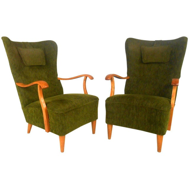 This pair of Mid-Century lounge chairs feature fantastic design, with high sculpted backs, wonderfully upholstered in...