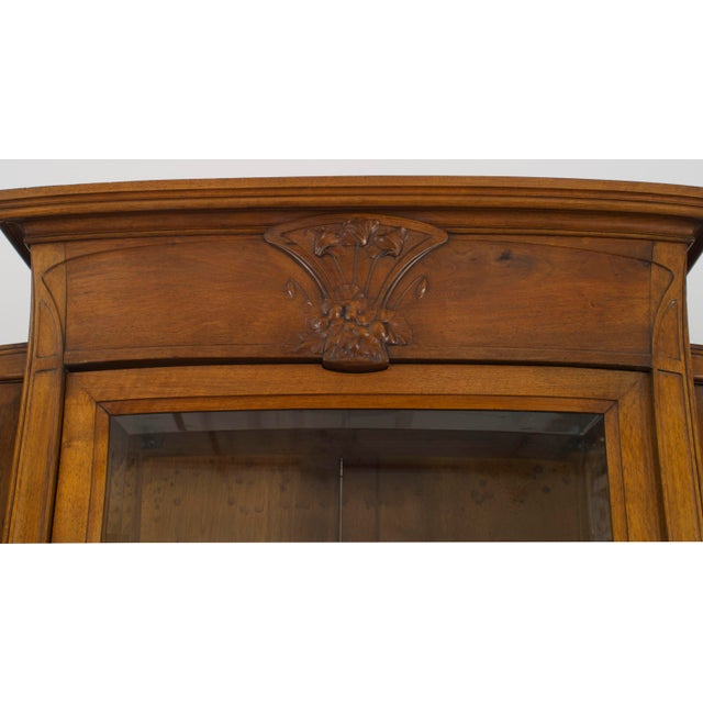 French Art Nouveau walnut display cabinet with 3 beveled glass doors and a floral carved center pediment and side corners