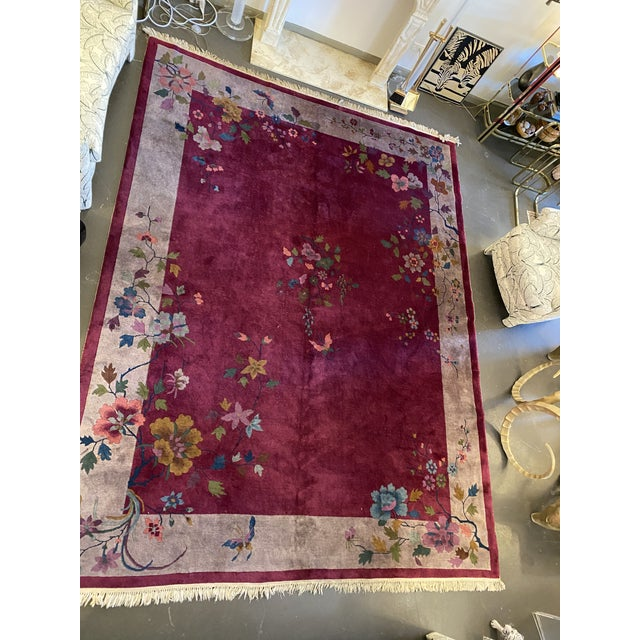 A vintage room size Chinese Art Deco rug with a floral and butterfly pattern on a wonderful brilliant burgundy / plum...
