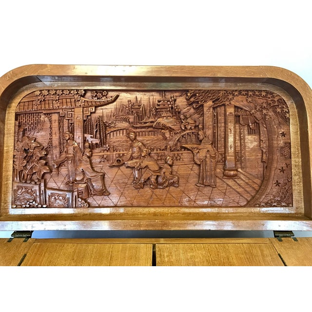Asian camphorwood bar cabinet with amazing intricately carved detail of Chinese family life. The top portion of the bar...