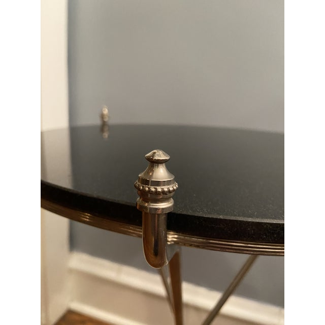 A beautiful Maison Bagues Hollywood Regency campaign table in nickel finish. Designed with a circular black granite top...