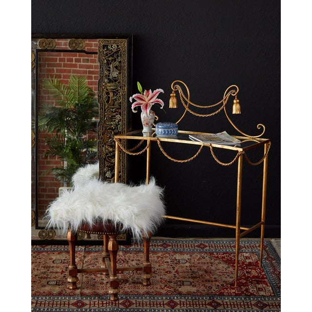 Diminutive gilt iron and faux rope vanity or console table made in the glamorous Hollywood Regency taste. Features a...