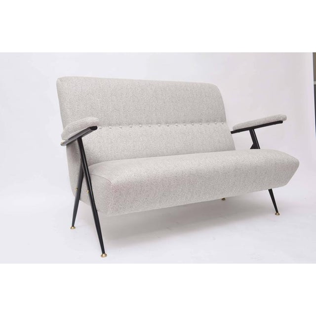 This handsome 1950s Italian settee with its angular black lacquered metal frame and brass detailing shares a striking...