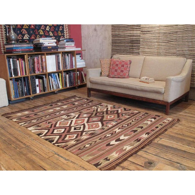 A lovely old tribal Kilim from Bowlan in Northwestern Iran with the characteristic diamond motifs, banded skirts and a...
