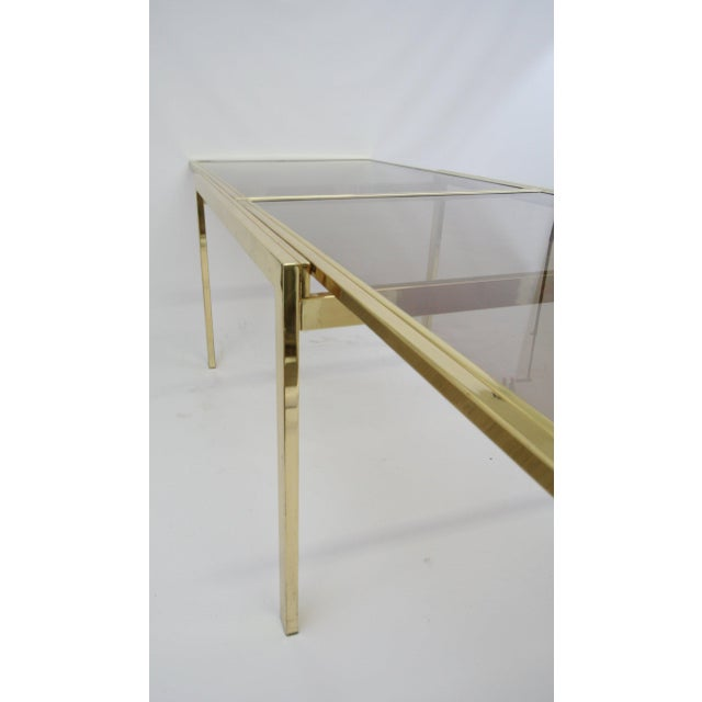 Dining table in polished brass finish with smoke glass top featuring a self extending top. Made by Design Industries of...
