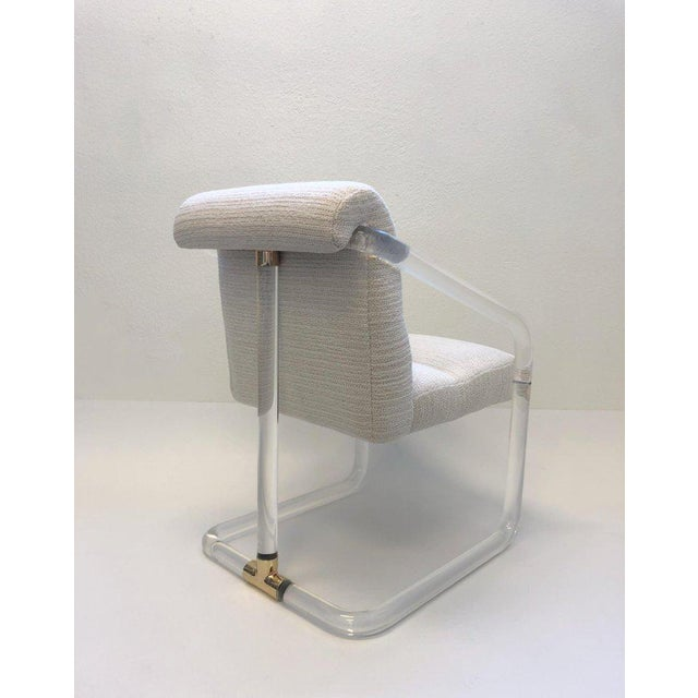 A glamorous set of four 1970s clear acrylic and polish brass arm chairs by Lion in Frost. This chair have been newly...