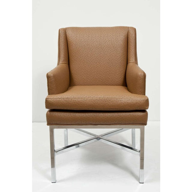 A handsome set of armchairs, attributed to Milo Baughman, with chrome legs and X-form stretcher, tight back with loose...