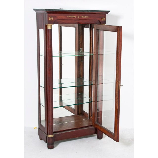 A 19th Century French Empire mahogany vitrine with gilt bronze mounts. The back of the vitrine is mirrored and it has...