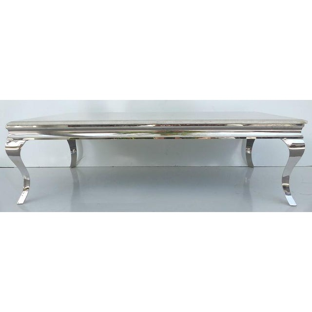 This is a large cocktail table with a lacquered faux-snakeskin finish. The top is lacquered marble and is supported by a...