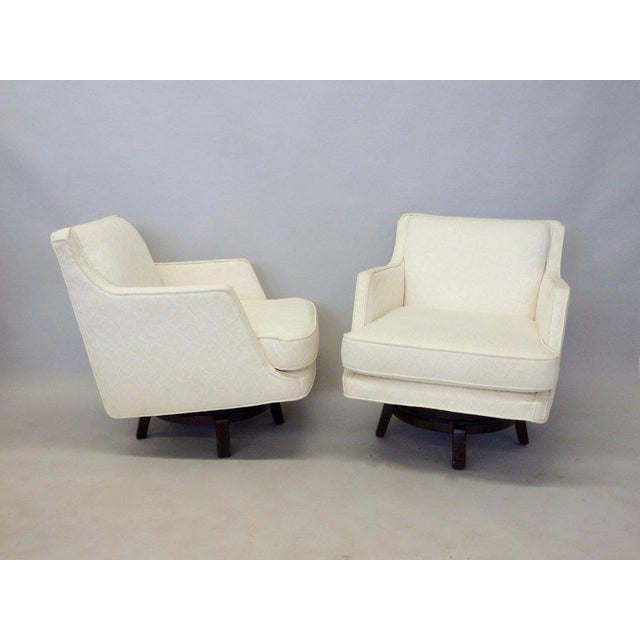 Pair of white edward wormley for dunbar swivel lounge chairs