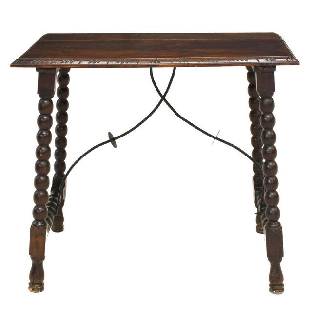Spanish side table from the late 19th c. Made Of oak, this table features a rectangular top rising on pad foot spool...