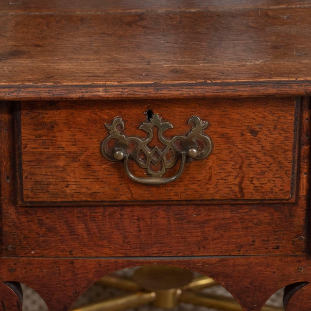 An early 18th century English lowboy dressing table, featuring three short drawers and brass Chippendale-style hardware...