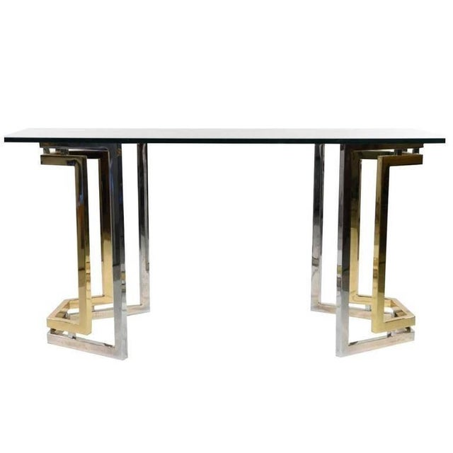 Pair of brass and chrome pedestals in the style of Romeo Rega with a glass tabletop for use as a dining table or desk....