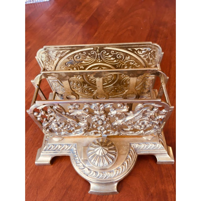 corative brass letter holder with inkwell and original glass liner. Double Griffins decorate the front panel.
