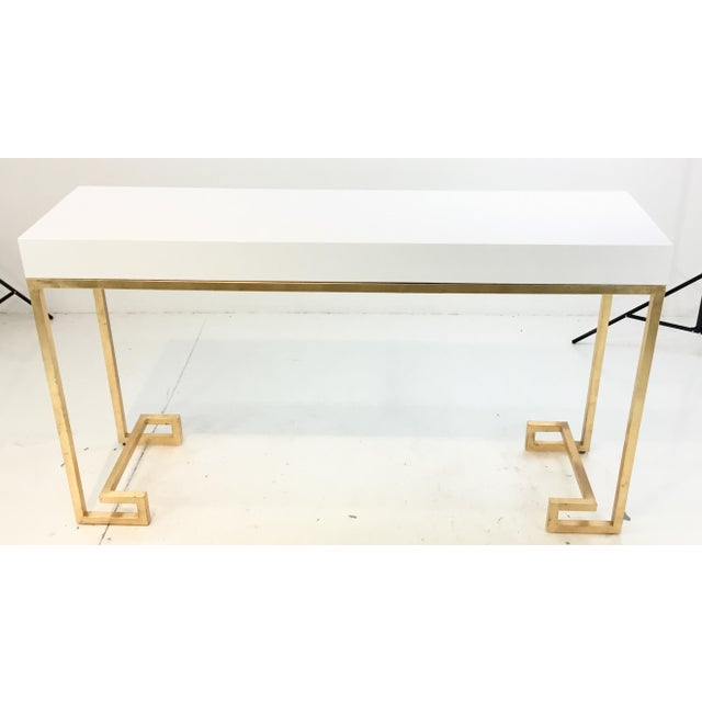 Stylish Worlds Away contemporary Barsanti white lacquer console table, gold leaf finished metal base with Greek key...
