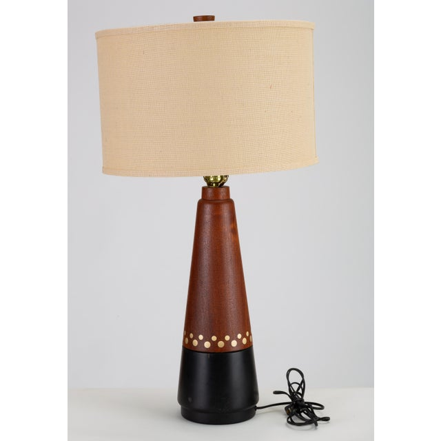 A large Danish Modern table lamp with a conical base in turned teak. Composed of two contiguous segments, the lower third...