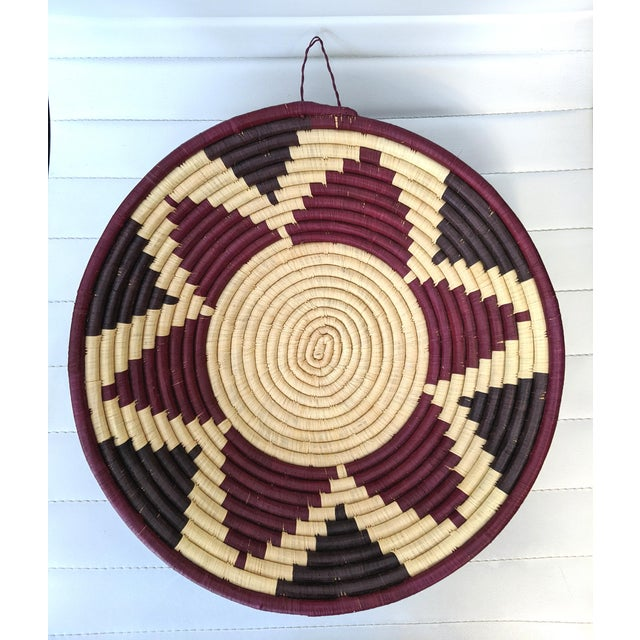 A stunning, artisanal coiled basket in hues of oxblood, eggplant and cream. Using traditional methods, Rwandan craftswomen...