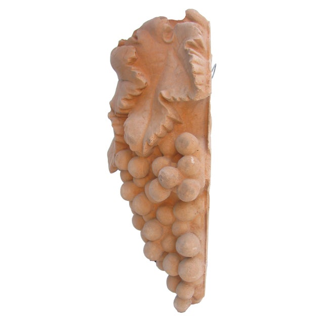 Unglazed terra cotta hanging wall planter in the form of a bunch of grapes with leafy vine. Center well opening at the top...