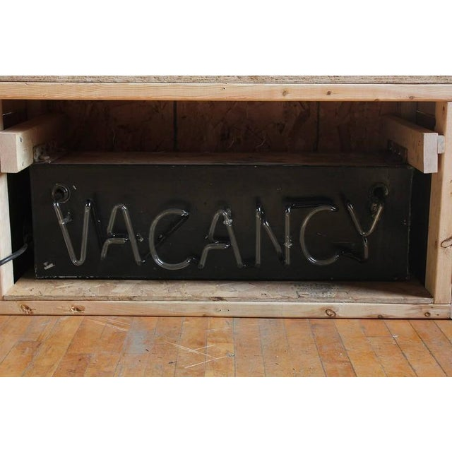 "1930s neon ""Vacancy"" sign with blinking light."