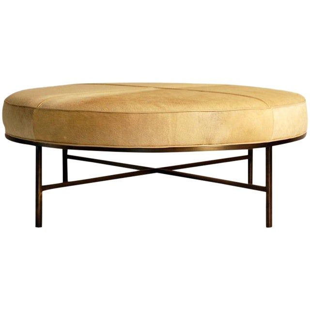 """The """"Tambour"""" natural hide and brass ottoman. This design pairs a raw natural hide surface with a chic antiqued brass base..."""