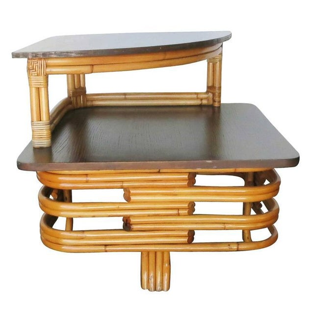 Vintage stacked cut-out rattan two-tier corner side table with mahogany top. Designed in the manner of Paul Frankl....