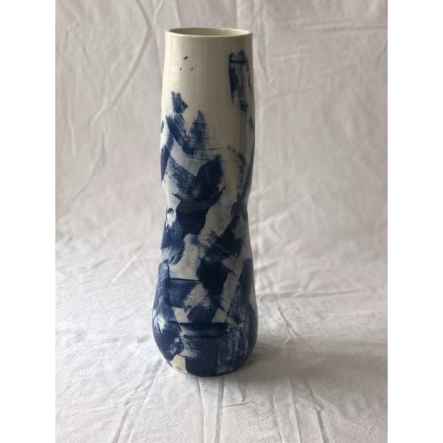 The surface of this tall curvy porcelain vessel is decorated with cobalt slip, which is partially wiped off before it is...