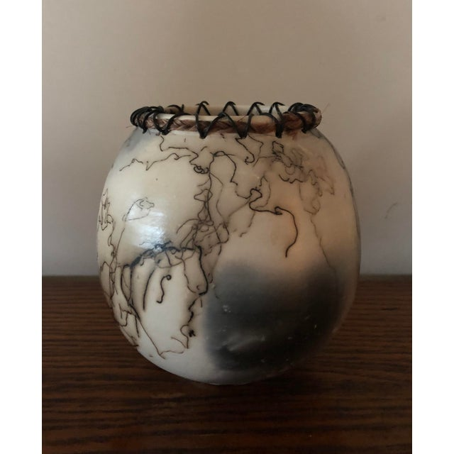 A stunning piece of pottery fired with horse hair to create a a pleasing and interesting view from every angle. The lacing...