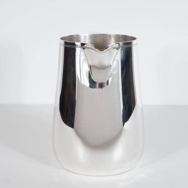 A fine Tiffany and Co. sterling silver 3 1/2 pint pitcher. Minimal detailing includes two fine etched bands along the...