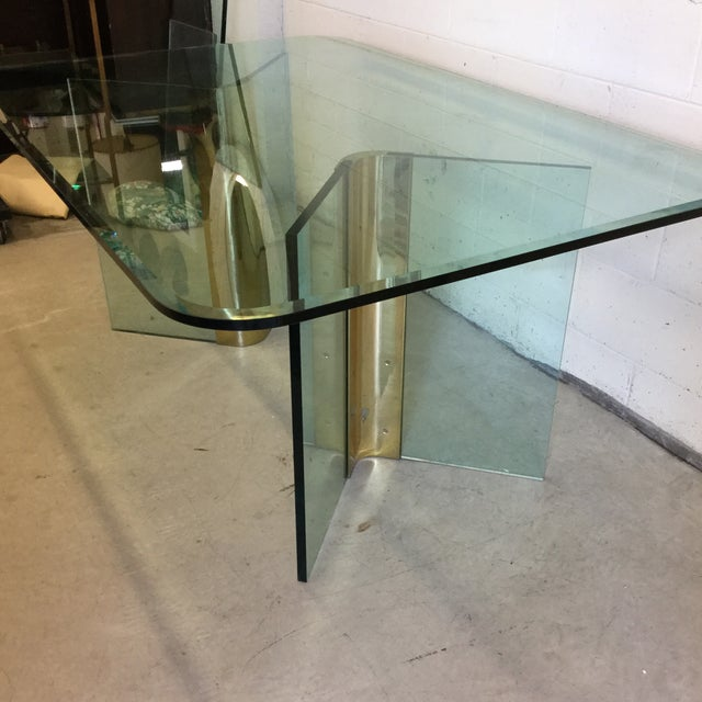 "You know the table. Brass brackets that the thick 1"" glass rests securely between and support the top. The brackets have..."