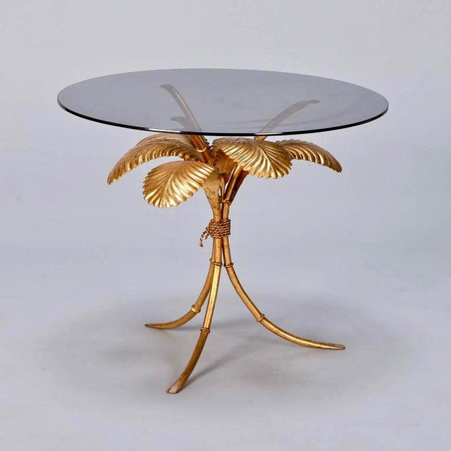 Mid-Century Italian side table has metal base with tripod legs and palm frond with gilt finish and round smoked glass...