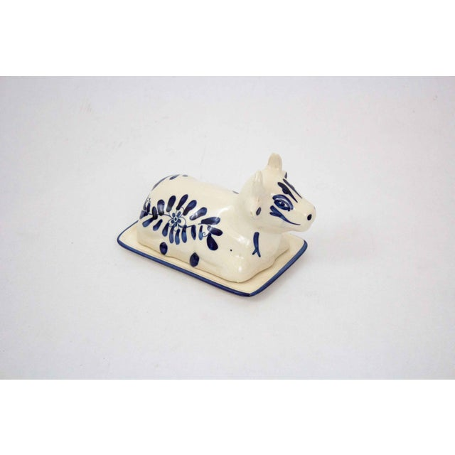 Mid century blue and white cow butter dish. The hand painted Dutch motifs give this piece a Delft-inspired feel. A...