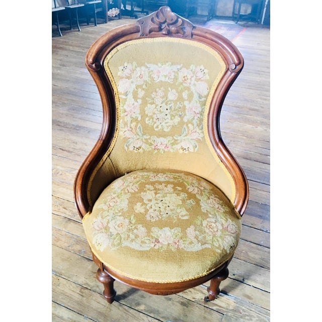 Carved walnut ladies slipper chair circa 1860. Delicately flowing lines and in like new condition. The upholstery is most...