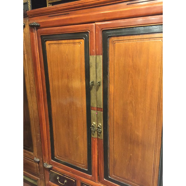 What a handsome piece in this elmwood armoire. Dark brown trim encases a rich honey tone insert. 3 drawers on the bottom...