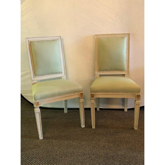 A set of 24 Hollywood Regency Jansen inspired parcel gilt and crème paint decorated side chairs. Each having new fabric...